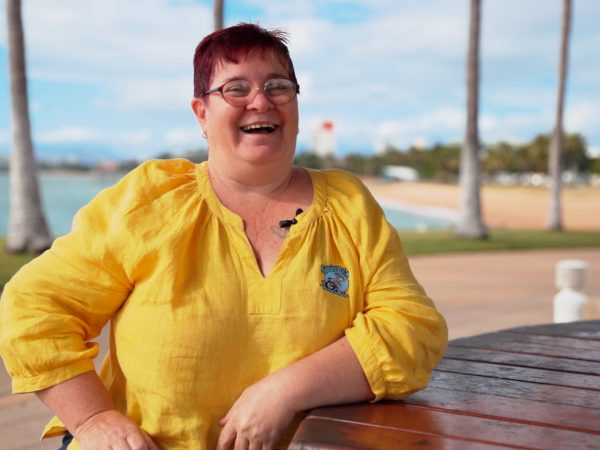 Sprint Rabbit boosts business with NEIS Sally poses at a picnic table on the Townsville foreshore in a yellow top.
