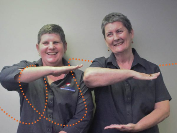 Two female My Pathway employees make equals signs with their hands and arms to show gender equality
