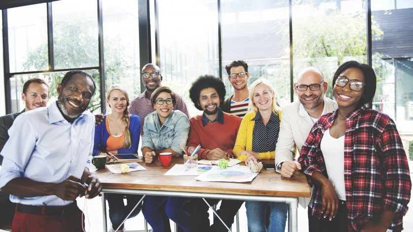 A diverse group of employees stand around a table and discuss managing generations in the workplace