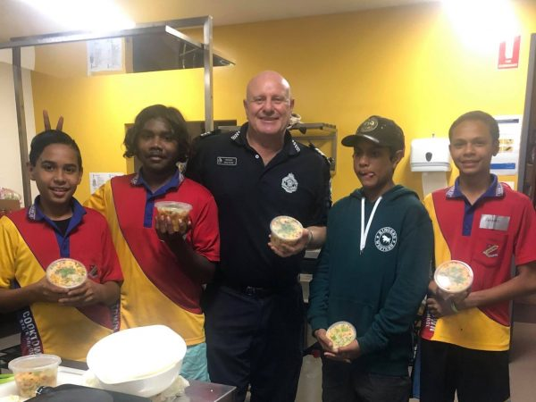 Sgt Dave Goode of Cooktown PCYC shows off a freshly cooked meal with four Indigenous boys in a bright kitchen